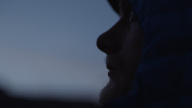 ecu. adventurer in hooded jacket looks out at the morning sky. - silhouette stock videos & royalty-free footage