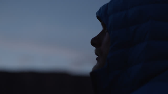 cu. adventurer in hooded jacket looks out at the morning sky. - profile stock videos & royalty-free footage
