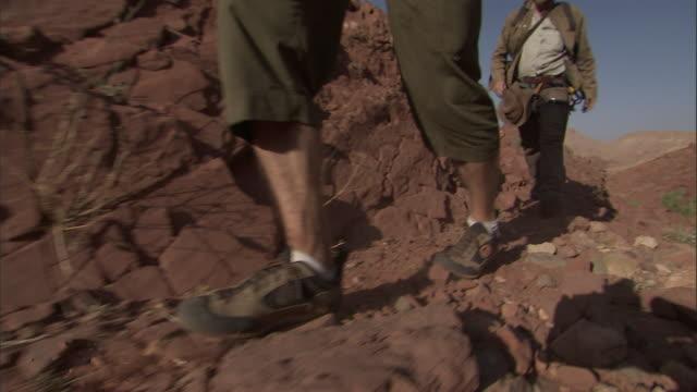 adventurers explore a red, rocky desert landscape. - rock stock videos & royalty-free footage
