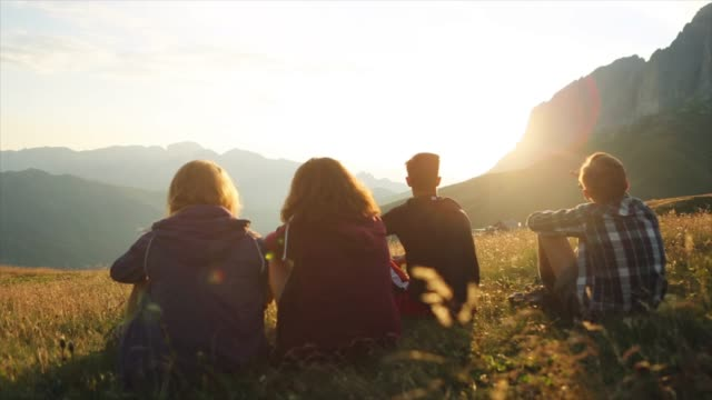 Adventures on the Dolomites: teenagers relaxing at sunset