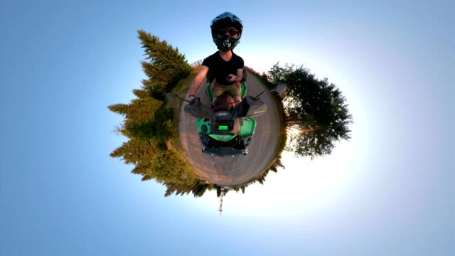 adventuring couple on a quadbike filming in little planet format - quadbike stock videos & royalty-free footage