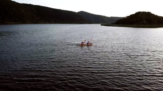 Adventurous couple paddling on the lake