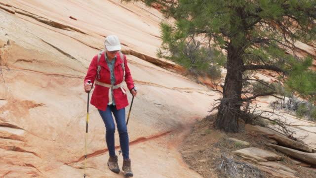 adventurous elderly lady walking down cliff with trekking poles in zion utah - sandstone stock videos & royalty-free footage