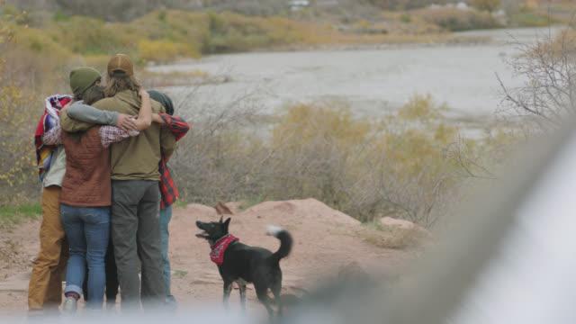 Adventurous friends share group hug at Utah camp site.
