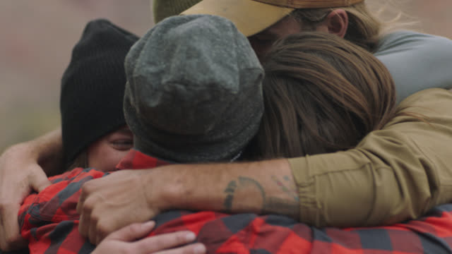cu. adventurous friends share group hug at utah camp site. - kompanjonskap bildbanksvideor och videomaterial från bakom kulisserna