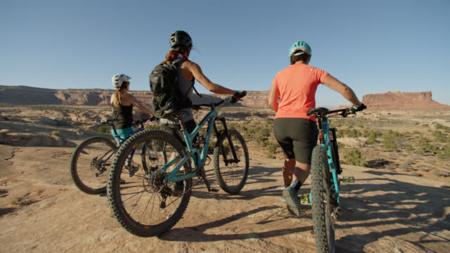 adventurous friends walk mountain bikes down rocky terrain overlooking scenic desert landscape. - terreno accidentato video stock e b–roll