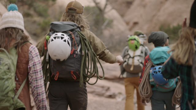 adventurous group of friends with rock climbing gear walk together up moab trail. - wilderness stock videos & royalty-free footage