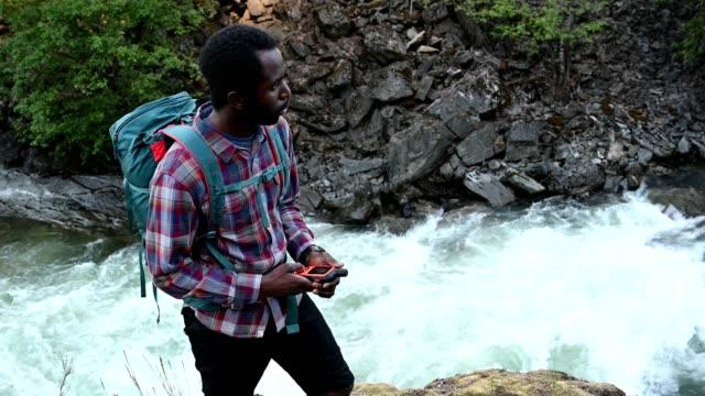 vidéos et rushes de homme aventureux utilisant le système de gps tout en faisant de la randonnée - remote location