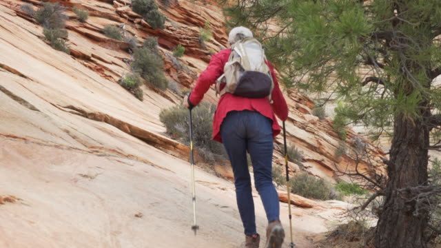 adventurous senior lady walking along rocky path outdoors in nature - sandstone stock videos & royalty-free footage
