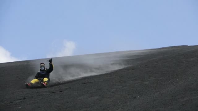 adventurous tourists sandboard down the cerro negro volcano in nicaragua sometimes reaching speeds up to 80 km/h - nicaragua stock videos & royalty-free footage