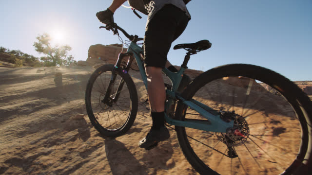 slo mo. adventurous woman bikes over mountainous terrain in moab. - mountain bike stock videos & royalty-free footage