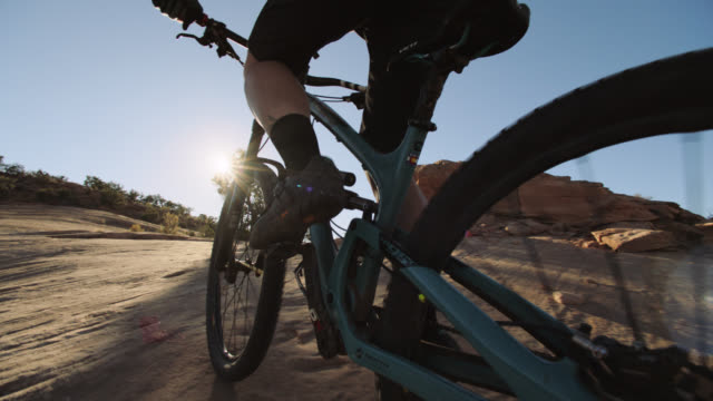 Adventurous woman mountain bikes over extreme terrain in Moab.