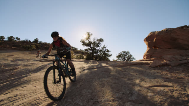vídeos de stock, filmes e b-roll de slo mo. adventurous women bike over mountainous terrain on the navajo rocks trail in moab. - terreno extremo