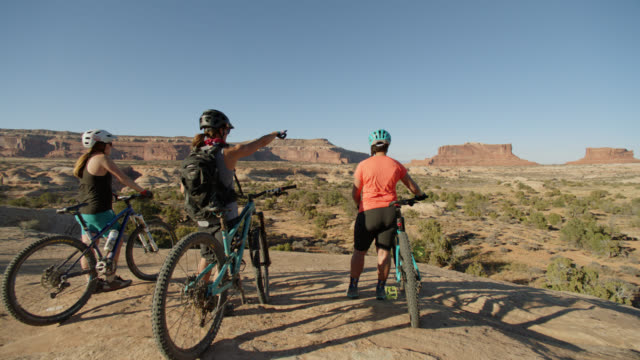 SLO MO. Adventurous women standing with mountain bikes point to distant buttes in Canyonland National Park.