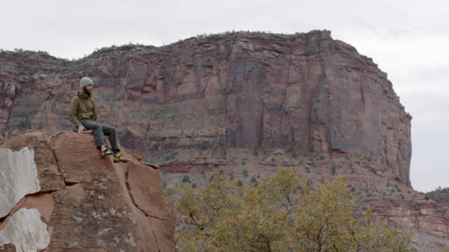 adventurous young man climbs to the top of rocky outcrop and sits overlooking rugged moab landscape. - butte rocky outcrop stock videos & royalty-free footage