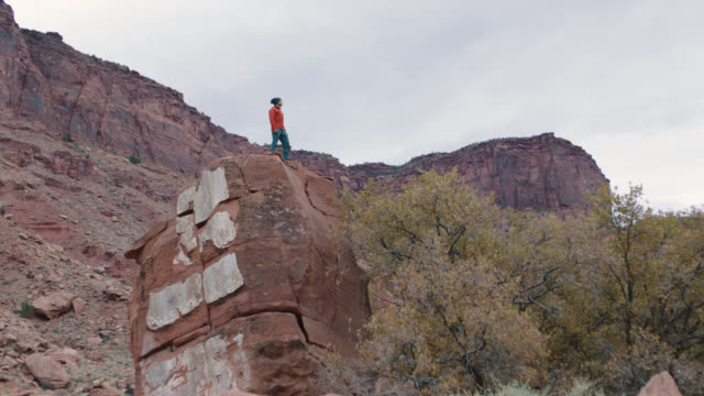 adventurous young man stands atop sandstone formation and surveys area in moab. - free climbing stock videos & royalty-free footage