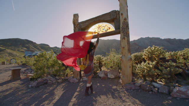 SLO MO. Adventurous young woman holds a flowing red scarf overhead in a desert ghost town.