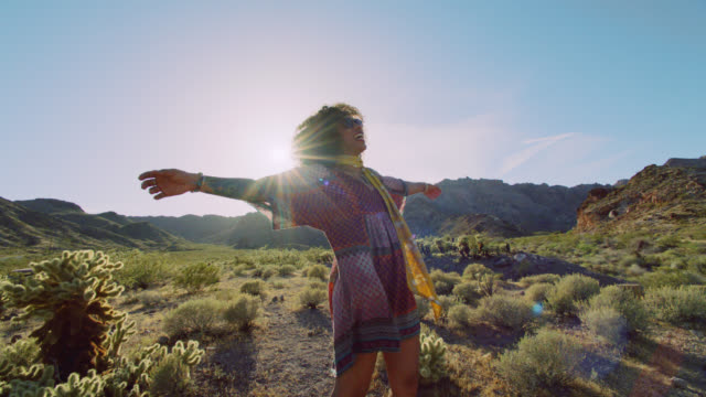 stockvideo's en b-roll-footage met slo mo. adventurous young woman laughs and twirls in the desert sun. - gekruld haar