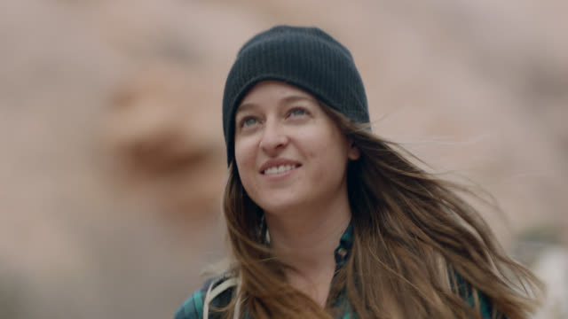 adventurous young woman on hiking trip turns to look around on moab trail. - drehen stock-videos und b-roll-filmmaterial