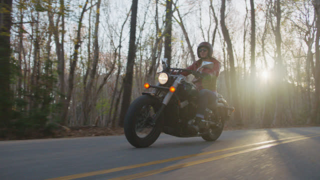 slo mo. adventurous young woman on motorcycle drives along wooded highway as setting sun peaks through trees. - motorradfahrer stock-videos und b-roll-filmmaterial