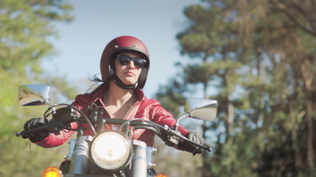 SLO MO. Adventurous young woman on motorcycle takes scenic drive along wooded highway.