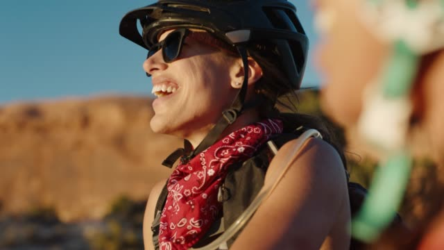 adventurous young women chat on moab mountain bike trail. - helmet stock videos & royalty-free footage