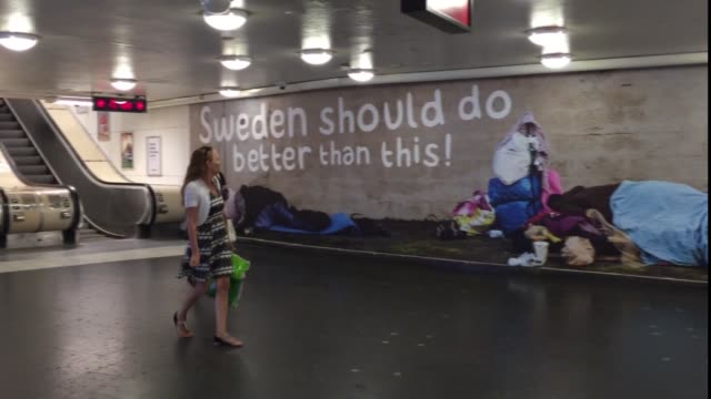 vídeos de stock, filmes e b-roll de advertisements placed by the swedish democrats party are seen on a wall and on the ceiling above the escalators leading to a subway station in... - mendigo