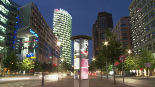 t/l, ws, advertising column spinning  on potsdamer platz at dusk, berlin, germany - colonna architettonica video stock e b–roll