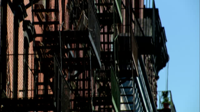 advertising signage hangs between fire escapes in lower manhattan. - fire escape stock videos & royalty-free footage