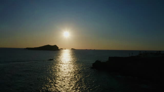 aereal - small boat crosses the sea at sunset - balearics stock videos & royalty-free footage