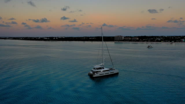 vídeos de stock e filmes b-roll de aerial: 360 degree view of boat sitting peacefully in rippling water as the sun sets on the cloudy horizon - providenciales, turks and caicos - vela desporto aquático