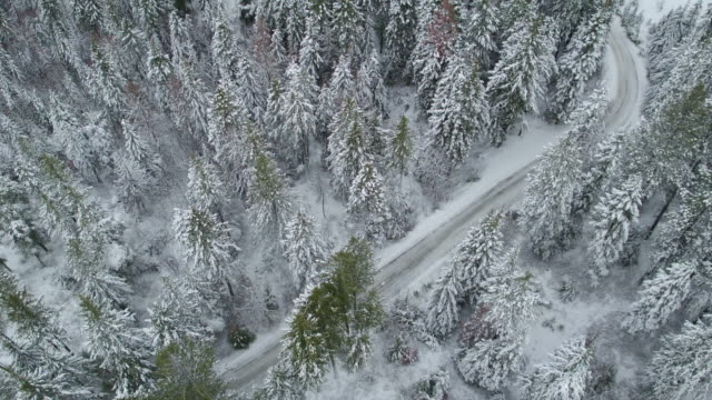 aerial 4k: establishing shot of a snow-covered road - thoroughfare stock videos & royalty-free footage