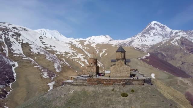 aerial 4k /gergeti trinity church, kazbegi mountain, georgia - religious symbol stock videos & royalty-free footage