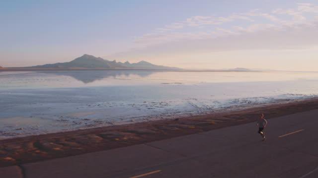 vídeos de stock, filmes e b-roll de antena 4k: fugindo do sol - motivação