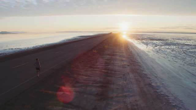 aerial 4k: running toward the sun - atletico video stock e b–roll