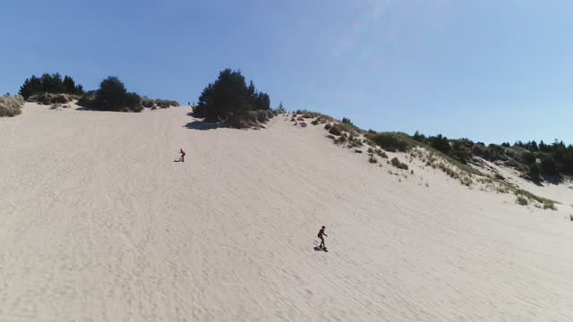 aerial 4k video of people sand boarding down sand dunes while on vacation - pacific islanders stock videos & royalty-free footage