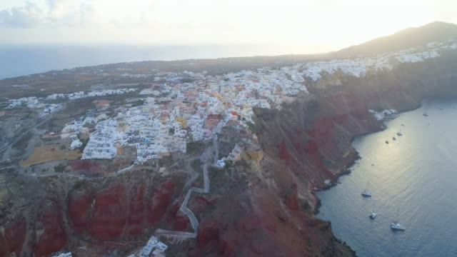 aerial: a bluff with homes on the top and boats below in santorini, greece - gebäudefries stock-videos und b-roll-filmmaterial