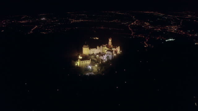 aerial: a castle lit up on a hill above the city in sintra - castle stock videos & royalty-free footage