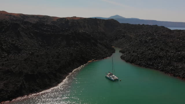 stockvideo's en b-roll-footage met aerial: a catamaran anchored in an inlet in paros - blijf staan