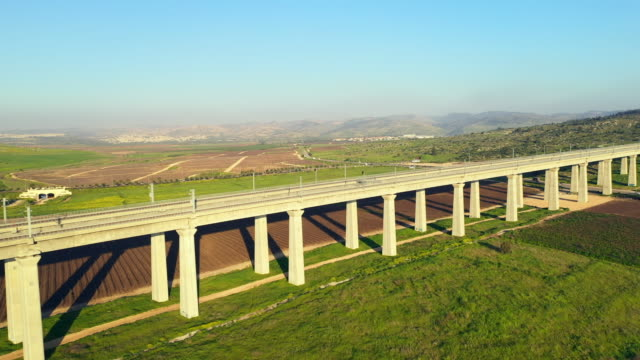aerial: a rail overpass cuts over lush fields and farmland on sunny day near modiin - nah stock-videos und b-roll-filmmaterial