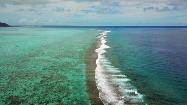 aerial: a reef break right off the island of moorea in the south pacific ocean - south pacific ocean stock videos & royalty-free footage