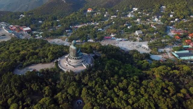 aerial: a village around the tian tan buddha statue - tian tan buddha stock videos and b-roll footage