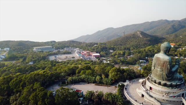 aerial: a village in a lush mountainside next to tian tan buddha statue - tian tan buddha stock videos and b-roll footage