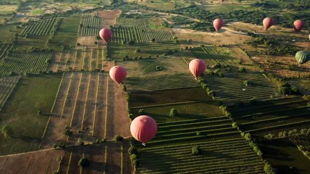 aerial: above a group of hot air balloons in old bagan - bagan stock videos & royalty-free footage