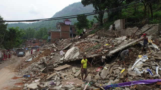 Aerial above street, rubble, destruction, people in street, May 2015, Nepal