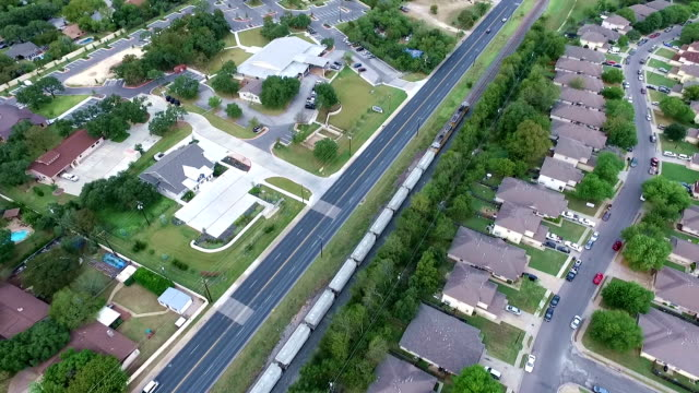 aerial above train passing across homes and houses in suburb new modern development in central texas outside of austin, tx diagonal - modern rock stock videos & royalty-free footage