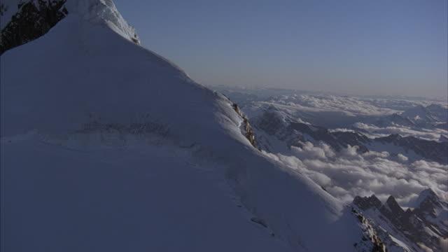 aerial across a snowy mountain ridge. - panorama stock-videos und b-roll-filmmaterial