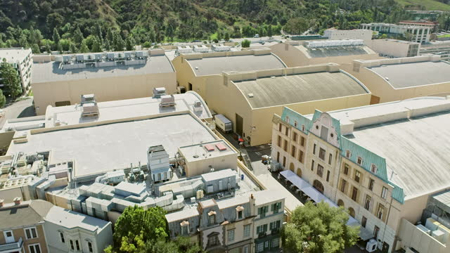 aerial across backlot structures built for exterior town square filming adjacent to movie studio sound stages - studio shot stock videos & royalty-free footage
