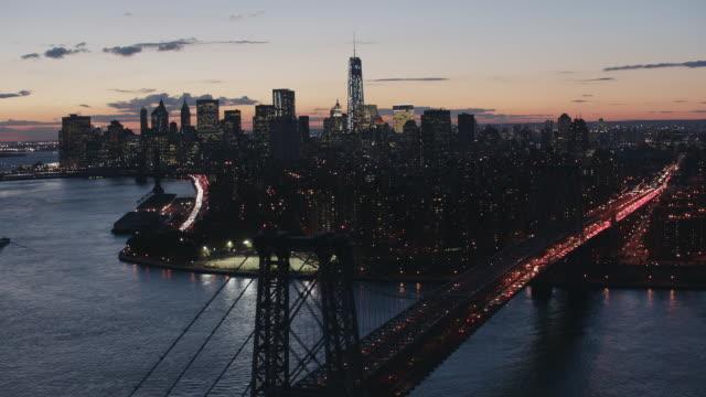 Aerial across East River following Williamsburg Bridge into Manhattan