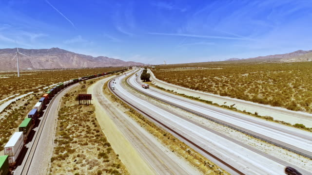 ws aerial across freight train and interstate 10 freeway looking west towards hotel tower of indian tribe casino in gorgonio pass - interstate 10 stock videos & royalty-free footage